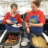Brats:  German Oberlander Club members Jeanie Hopper and Brenday Bryant serve bratwurst and potato salad Thursday afternoon at the annual Strassenfest.
