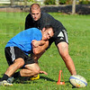 Practice make perfect: Garrett Fredrick(in blue) and Kris Kulich struggle for the ball during rugby practice Wednesday evneing.