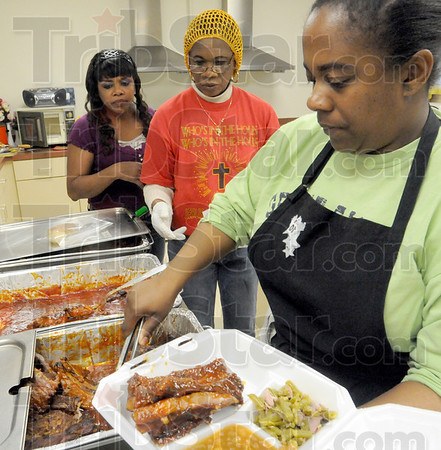 To go: Amanda Ladd (L) and Cynthia Handley wait for the mealing being dished by Leah Bragg during Saturday's annual barbeque event at Allen Chapel.