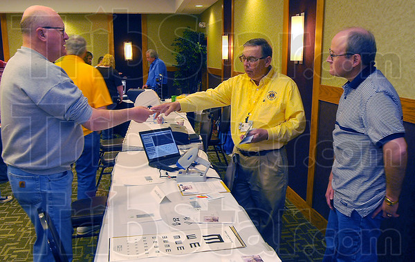 Call me: Scott Greenwell accepts Ray Collins' business card at teh Vision Expo Wednesaday afternoon. Collins and Rodney Frakes, right are with teh Vigo County Lions Club. THey were at eh expo letting visitors know about thei4r vision care servces. The device in front of Cillins can perform a vision test on very young children, checking for problems in sis areas including near-and far-sightedness, lazy eye and the eyes' prescription.