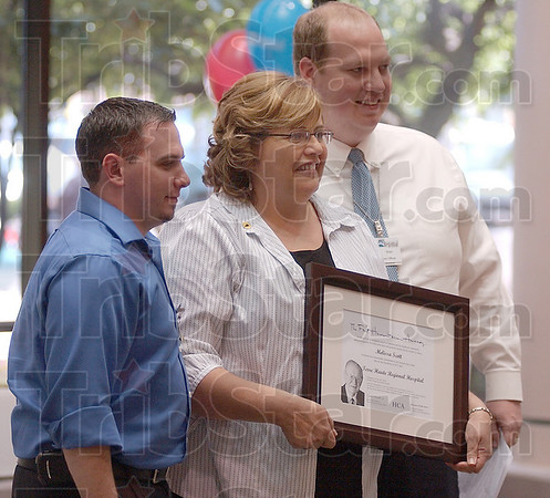 Valued: Regional Hospitals' Melissa Scott, center was one of three receipients of the Frist Award Wednesday. The parent company, Hospital Corporation of America, gives out the humanitarian awards. With her are Aaron Garofola, HR Director and Brian Bauer the hospital CEO.