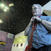 Tied down: Doug Lawhead ties his necktie after setting his exhibit at the Arts Center in Palestine, Ill. Friday evening.
