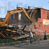 Part tense: Demolition workers pull down the Pastime Tavern after part of it crumbled in the high winds earlier Tuesday.