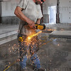 Sparks, not sawdust: Carpenter Larry Gossett cuts a notch in a steel beam that will form part of the office in the new street department garage. The property was recently deeded to the city from Vigo county even though the city has used the property for decades.