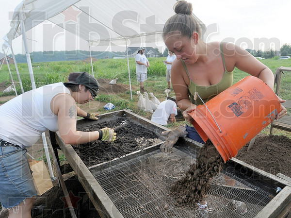 Screening: ISU students Heather May and Amber Ballinger pour excavated dirt onto a screen to sift out remnants of times gone by.