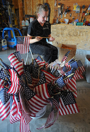 Getting ready: Olivia Goulding works in her garage Thursday evening, threading name tags on the staffs of flags. The flags will be placed at Memorial Staduim this evening, in preparation for Saturday's Run for the Fallen.