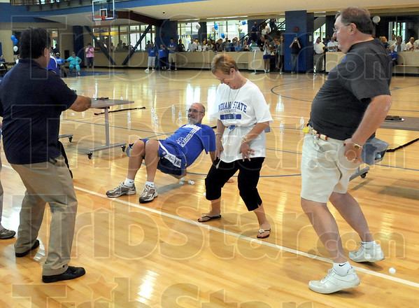 """Junk in the trunk: Indiana State University president Daniel Bradley sits down to dump the """"junk in his trunk"""" as others simply shake during a back-to-school event at the Student Rec Center."""