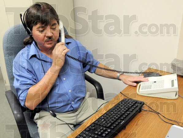 Hello, Hamilton Center: Randy Berg answers an incoming telephone call from his work area in Hamilton Center Thursday afternoon.