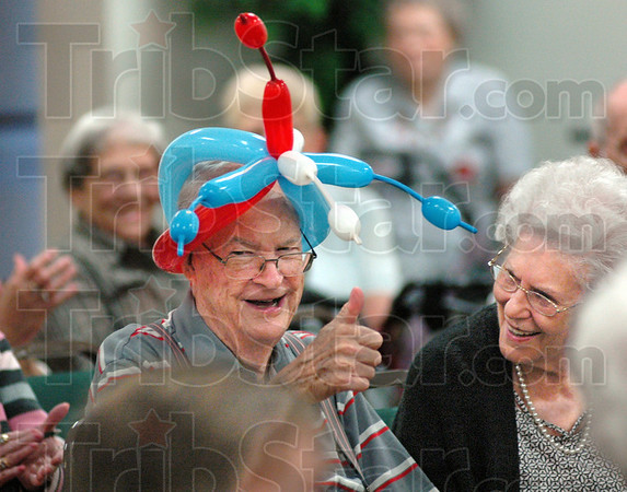 """Thumbs up: Westminister resident Harry Gee is a good sport and gives the """"thumbs up"""" with the approval of fellow resident Simone Cline after receiving a balloon hat from Harpo the clown Thursday."""