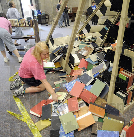 Dumped: Sarah Galloway picks up book that were thrown from their shelving when one collapsed causing a domino effect on the second floor of the Cunningham Memorial Library on the ISU campus Thursday.