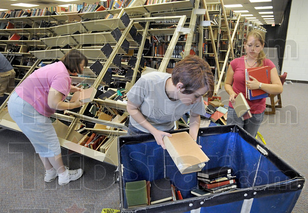 Clean-up: Vickie Magill, Allison Conner and Elizabeth Powers carefully remove books from tilted shelves on the second floor of the Cunningham Memorial Library Thursday afternoon. The shelves fell over dumping thousands of books on the floor.