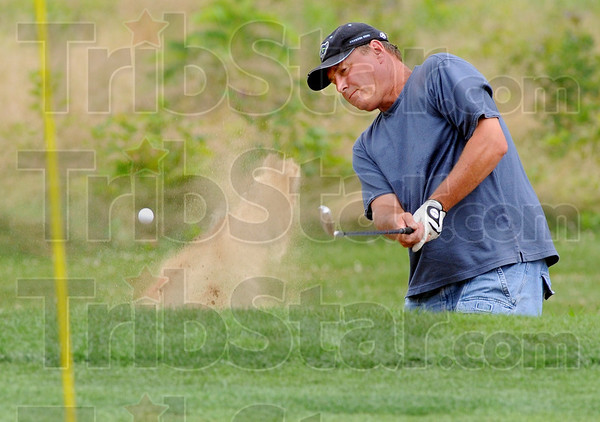 Sandblaster: John Tackett hits a shot from the sand trap on the 9th hole at Hulman Links Sunday afternoon during  Men's Senior City Golf Championship play.