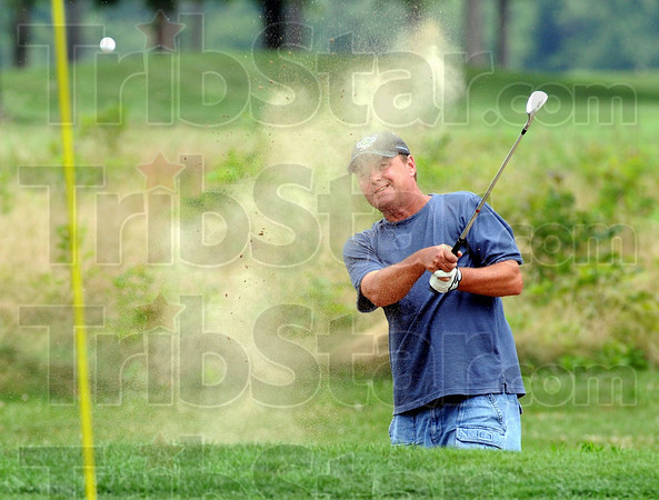 Sandman: John Tackett watches the flight of his ball as he blasts out of the sand on the 9th hole at Hulman Links during the Men's Senior City Golf Championship.