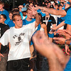 Tribune-Star/Joseph C. Garza<br /> High five welcome: Indiana State freshman Broc Tarwacki of South Bend high-fives a member of the welcoming committee Sunday near the university's arch at Third and Cherry Streets.