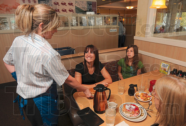 Tribune-Star/Joseph C. Garza<br /> Fresh stack: IHOP server Wendy Dispennett delivers a fresh stack of pancakes to customer Sondra Blake, 20, of Clinton during the lunch hour Sunday at the Third Street restaurant. During the month of September, the restaurant will donate one dollar for every customer served to a local charity.