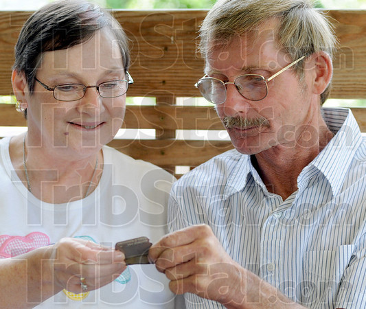 """Dad's tags: Diana Stephens and her brother James Sutherland look at their father's replacement """"dog tags"""" on the front porch of their northside home Thursday afternoon. Their father's original tags have been found in France."""