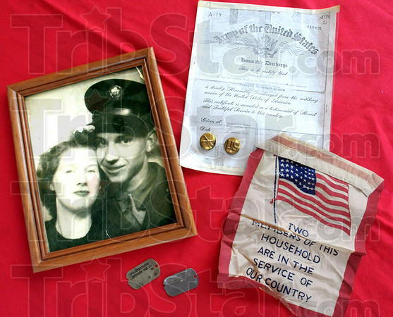 Memorabilia: A photograph, discharge papers, replacement dog tags and banner are part of the memorabilia of James L. Sutherland's war experience.
