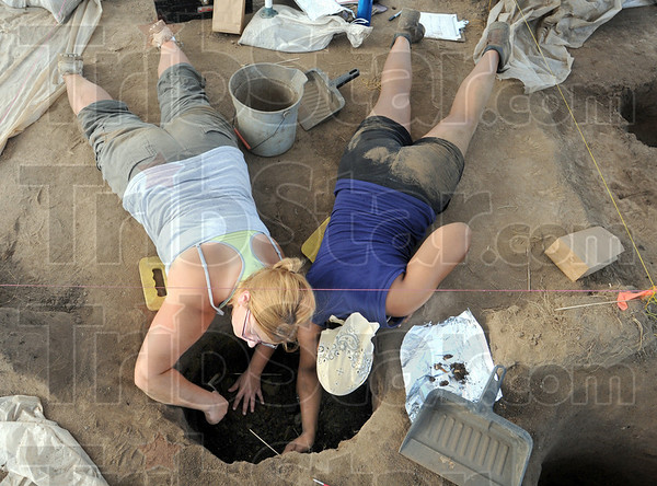 Doing the dirty work: Indiana State University students Stephanie Skava and Shannon Rosser work on an archelogical dig in North Terre Haute Tuesday morning.