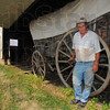 Prized posession: Norman Skinner stands by a circa 1851 Conestoga wagon. The piece is justone of hundreds of items that are on display today and Sunday at his Steam Harvest Days in northern Vermillion county.