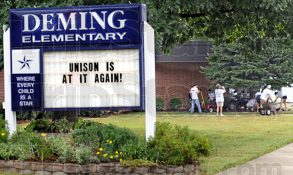 Again: Unison volunteers work on landscaping at Deming Elementary School Saturday morning. About 30 volunteers from Unison and Duke Energy worked to install a new playground and landscaping Saturday.