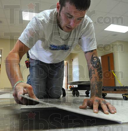 Flooring: Doug Bowden lays tile in the new Booker T. Washington school.