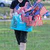Getting ready: Olivia Goulding carries a basket of flags to their point on the Indiana Mile at Memorial Stadium Friday evening. Scores of volunteers were helping place some 6,000 flags for Saturday's Run For The Fallen.