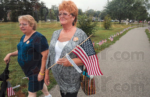Tribune-Star/Joseph C. Garza<br /> For Kyle: Nancy Knight, the mother of the late Sgt. Kyle Childress, carries his flag with the attached name tag during the Run for the Fallen Saturday at Memorial Stadium.
