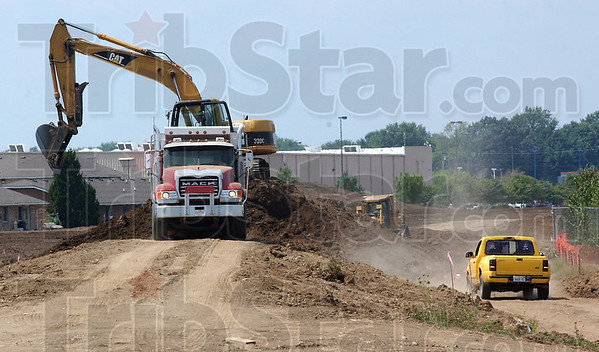 Work goes on: Excavators, dump trucks and bulldozers work to raise the levee lining Thompson Ditch Thursday afternoon.