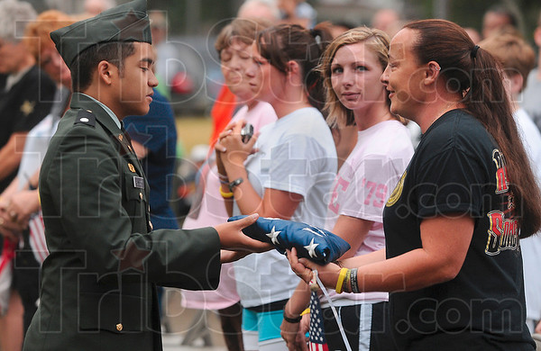 Tribune-Star/Joseph C. Garza<br /> On behalf of a grateful nation: Cadet 2nd Lt. Stevie Poinsett of the Terre Haute South High School Army Jr. ROTC presents a flag to Kim Stultz, the mother of the late Cpl. Gregory Stultz of the United States Marine Corps, after a flag folding ceremony Saturday at Memorial Stadium.