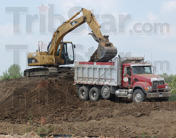 Higher ground: An excavator loads fill dirt into a dump truck along Thompson Ditch Thursday afternoon. Work continues along both sides of the ditch from South 7th Street to US 41, raising the levee.