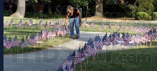 Preparations: Lori Rourke straightens flags along the Indiana Mile at Memorial Stadium Friday evening. She brought her Boy Scout Troop 17 to help place the flags for Saturday's Run For The Fallen.