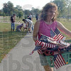 Labor of love: Volunteer Lori Davignon carries a basket of named flags to their place on the Indiana Mile Friday evening. Volunteers worked placing the flags until finished, around midnight. Some of the holes for the flagstaffs were made with a hammer and a screwdriver, others were formed with drills and long bits.