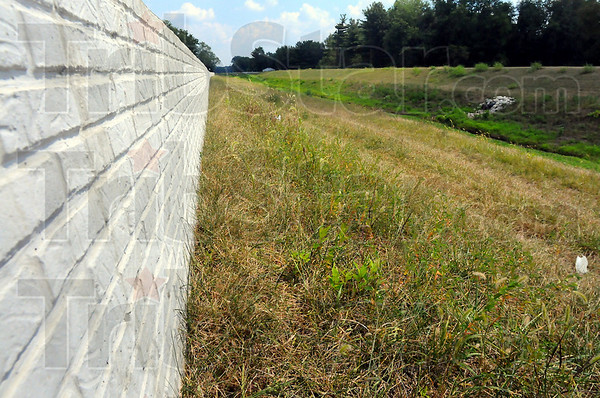 Completed: A concrete wall tops the south side levee of Thompson Ditch upstream from 7th Street.