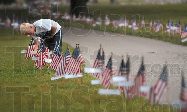 Tribune-Star/Joseph C. Garza<br /> Looking for family: Evan Burbrink, 7, looks at one of the over 6,000 name tags of a fallen service member during the Run for the Fallen Saturday at Memorial Stadium. Burbrink and his mother, Amber Burbrink, were looking for a cousin, the late Staff Sgt. James Patton who was killed in Iraq.