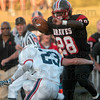 Tribune-Star/Joseph C. Garza<br /> Terre Haute South's Tyler Evans tries to avoid the tackle by North's Austin Lewis (23) during the Braves' annual game against the Patriots Friday at Memorial Stadium.