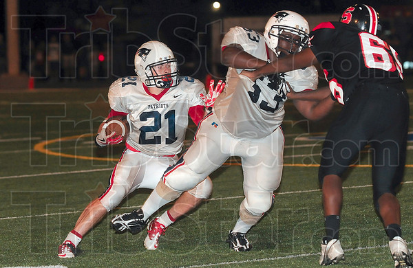 Tribune-Star/Joseph C. Garza<br /> Looking for running room: Terre Haute North's Daniel Gabbard looks for an opening as teammate Jabari Bradshaw  blocks South's Elijah Beard during the Patriots' win Friday at Memorial Stadium.