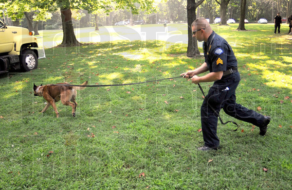 Drug search: Terre Haute police Sgt. Todd Haller follows his K-9 to a vehicle where drugs have been hidden during a demonstration of the dogs ability to find them.