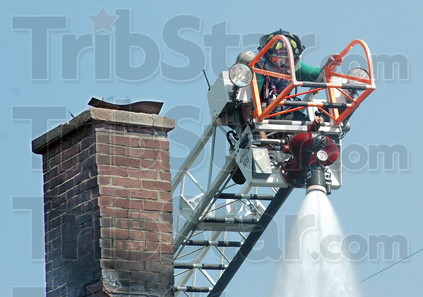 Hot spot: A firefighter works in sweltering heat with breathing apparatus for fresh air at the scene of a residentail house fire Wednesday evening.