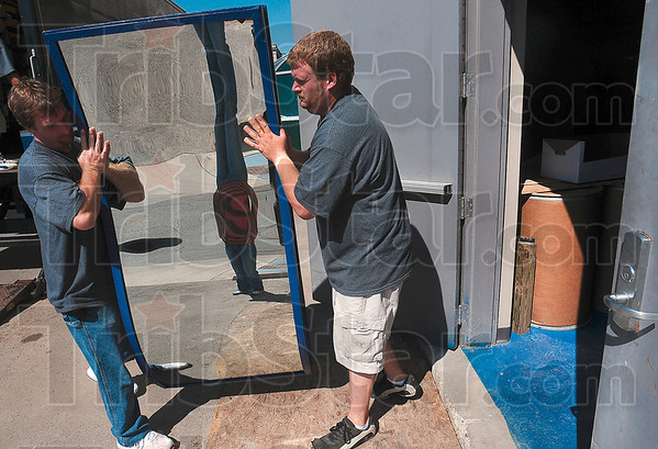 Tribune-Star/Joseph C. Garza<br /> A reflection of fun (and learning): Eldred Moving & Delivery employees John Warnock and John Ahlers, Jr., move a funhouse mirror into the new Terre Haute Children's Museum Wednesday morning. The museum is scheduled to be open Sept. 24.