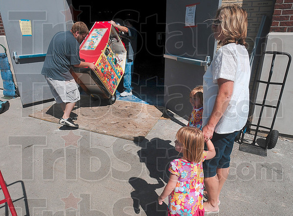Tribune-Star/Joseph C. Garza<br /> A new home for the bubble gum machine: Bridgett and Vanessa Eldred watch with their grandmother, Debbie Eldred, as Eldred Moving & Delivery employee John Ahlers, Jr., helps move in a bubblegum machine into the new Terre Haute Children's Museum Wednesday.