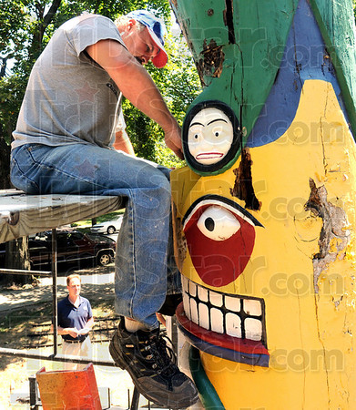 Dig it: Tom Eversole is part of a restoration crew from Pruitt Properties complet restoration that is in the process of repairing the totem pole at the Vigo County Historical Museum.