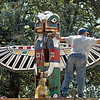 Wingspan: Tom Eversole reaches to the tip of the wing on the totem pole in front of the Vigo County Historical Museum Wednesday afternoon. He and a crew are in the process of restoring the piece after it has suffered from weather changes over the years.