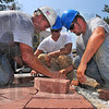 Hands on instruction: Chuck Morris, an instructor at the Indiana Labor Training Institute, works with apprentices Dustin Richards and Matt Crawford. They are part of a volunteer team laying the brick walkway around the Max Ehrman sculpture at 7th and Wabash. Boral Brick donated some 7,000 bricks. Other donations came from S&G Excavating and S.T. Construction. Metzger Landscape will put the finishing touches on once the bricks are in place.