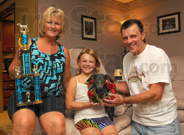 All in the family: The Kaperak family, Cheryl, daughter Kalea and Dennis pose with Mr. Reggie in their Terre Haute home Monday evening. The dachshund won the Ellis Park sixth annual dachshund races Saturday, outsprinting 31 other weiner dogs.