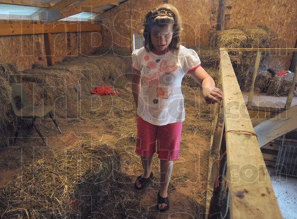 Hay loft: Jodi Jones feels her way along a railing in the hay loft of the family barn Saturday afternoon. Jodi feeds her animals without assistance.
