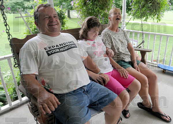 Happy days:  Mike and Bobbi Jones laugh as they swing with daughter Jodi on the front porch of their Marshall, Ind. home Saturday afternoon.