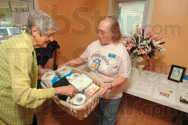 Tribune-Star/Joseph C. Garza<br /> A little something for the grand re-opening: Dorothy Jerse presents a basket of paper goods to Muriel Ryan, executive director and founder of Families by Choice, during the grand re-opening of Deborah's House Monday on south 11 1/2 Street.