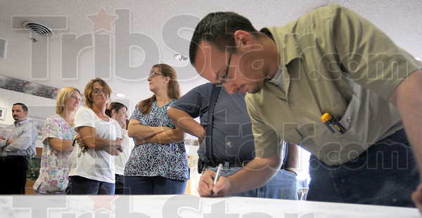 Petition line: Royal Oaks employee Jeff Stacy signs the petition at the facility as others line up to do the same Tuesday afternoon.