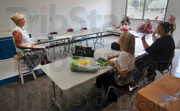 Tribune-Star/Joseph C. Garza<br /> Flip flops are now allowed!: Sheri Montgomery, director of the Booker T. Washington High School nursery, goes over the rules for the new school year with students Tuesday morning.