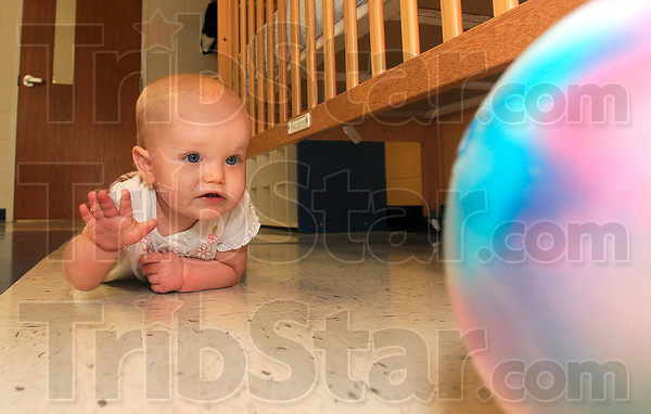 Tribune-Star/Joseph C. Garza<br /> Mom learns, I play: Eleven-month-old Emma Cox chases after a ball in the Booker T. Washington High School nursery Tuesday morning.